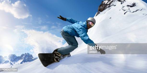 fast moving snowboarder in motion close up during turn - boarding stock pictures, royalty-free photos & images