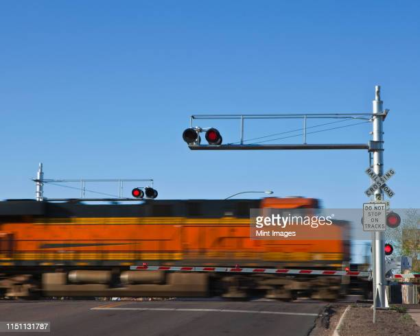 fast moving train at a railroad crossing - railroad crossing stock pictures, royalty-free photos & images