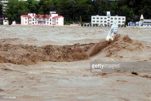 Fast moving water flows over a Hindu statue during a heavy monsoon rain in Rishikesh town in the Indian state of Uttrakhand on June 17, 2013. Heavy...