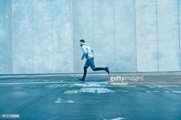 Fast runner makes his way past a big grey concrete wall