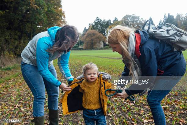 fastening up his jacket - babyhood stock pictures, royalty-free photos & images