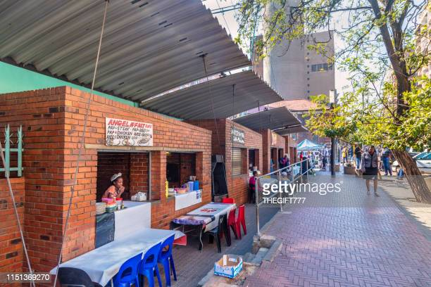 fastfood vendor in a kiosk in the streets of hillbrow, johannesburg - gauteng province stock pictures, royalty-free photos & images