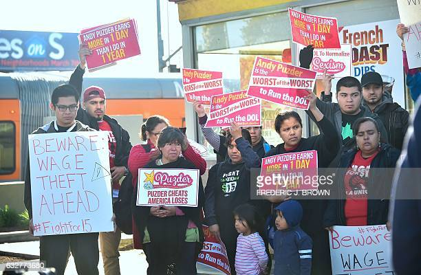 Fastfood workers hold placards and shout slogans protesting against fast food mogul Andy Puzder as President Donald Trump's nominee for labor...