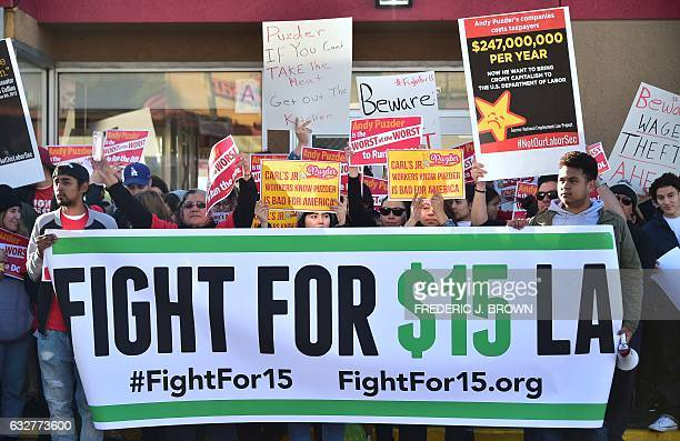 Fastfood workers in the fight for $15 USD per hour wage hold placards and shout slogans protesting against fast food mogul Andy Puzder as President...
