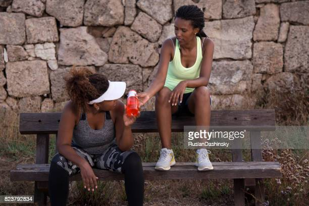Fat and slim women taking a break after a run.