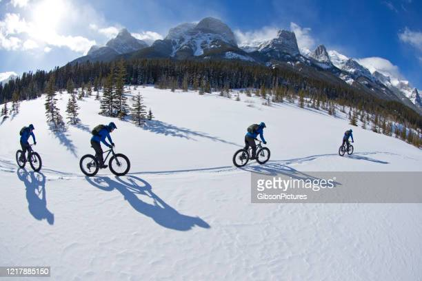fat biking at the canmore nordic centre - multiple exposure sport stock pictures, royalty-free photos & images
