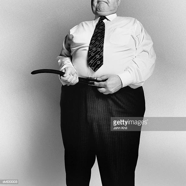fat businessman fastening his belt - tighten stock pictures, royalty-free photos & images