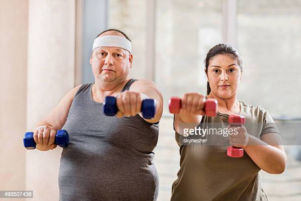 Fat couple exercising with dumbbells and looking at camera.