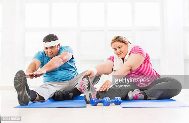 Fat couple stretching.