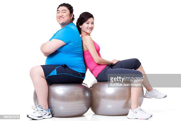fat man and girlfriend sitting back to back on fitness balls - skinny man fat woman stock pictures, royalty-free photos & images