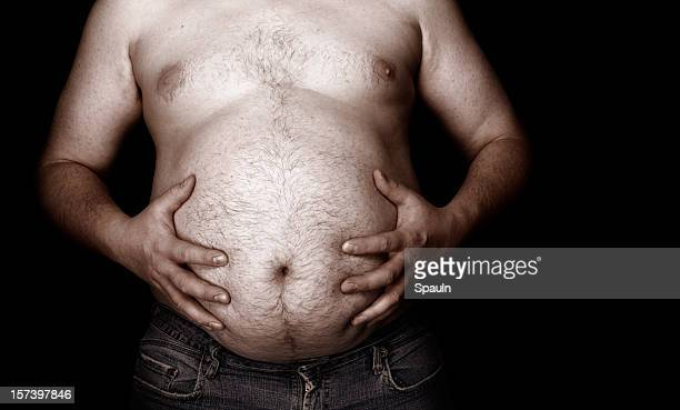 Fat man holding his stomach with jeans