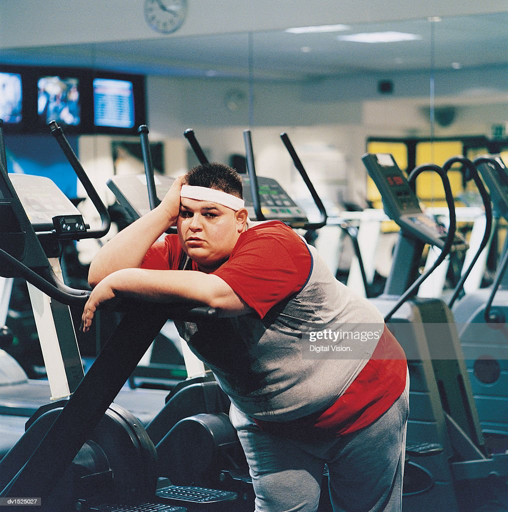 Fat Man Leaning Against a Running Machine : Stock Photo