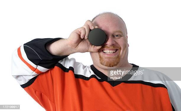 fat man smiles with hockey puck - ijshockeytenue stockfoto's en -beelden