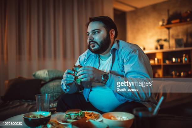 fat man watching tv - over eating stock pictures, royalty-free photos & images