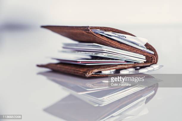 fat wallet with numerous credit cards - colin hawkins stock pictures, royalty-free photos & images