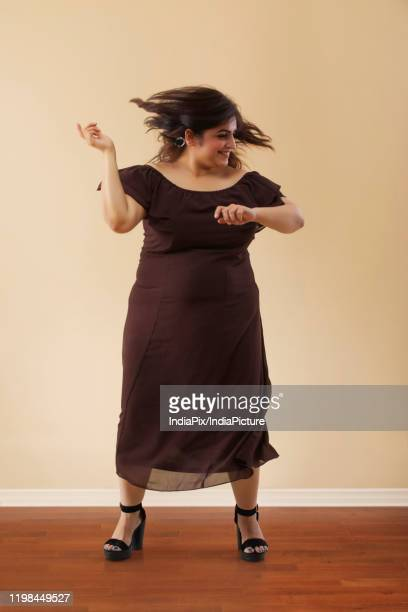 fat woman in a long brown dress dancing on high heels - fat women in high heels stock pictures, royalty-free photos & images