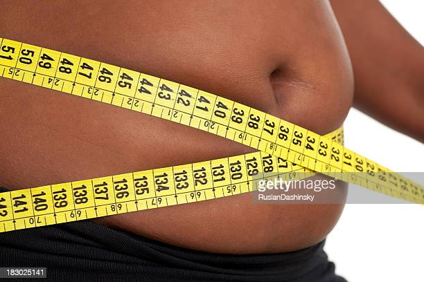 fat woman measuring her waist. - images of fat black women stock photos and pictures
