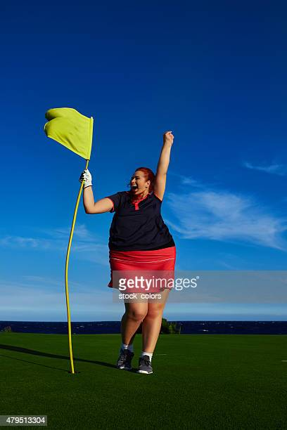 fat woman near golf flag cheering - golf flag stock photos and pictures