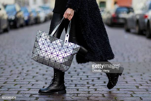 Fata Hasanovic wearing a black long fluffy jacket sassy classy black long shirt silver hand bag black leather pants and black heavy boots from sassy...