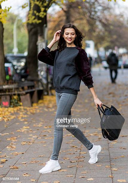 Fata Hasanovic wearing a sassy classy scarf, a grey purple velvet sweater, grey skinny Dr. Denim jeans, white Nike sneaker, black Asos bag on...