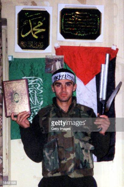 Fatah activist 22yearold Amer Shkokany from the West Bank town of Al Bireh is shown with a Koran and weapons May 24 2002 Shkokany was named as the...