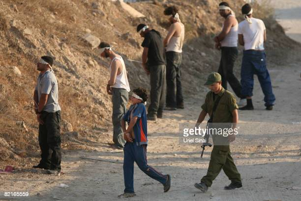 Fatah fighters who fled from Hamas gunmen in the Gaza Strip during the night and a young boy are detained at an Israeli army base on August 3 2008 at...