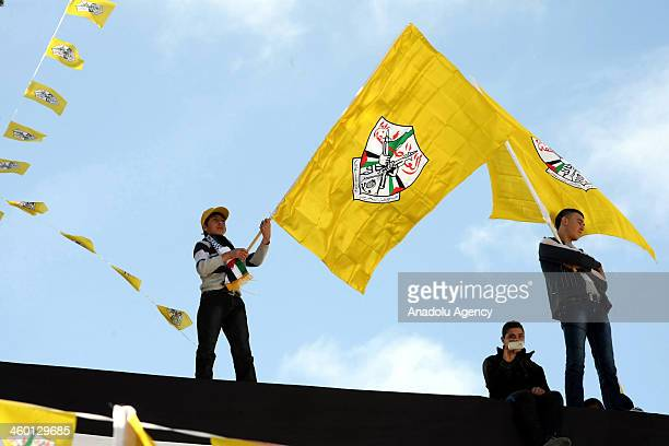 Fatah supporters wave flags during a rally marking the 49th anniversary of the Fatah movement in the West Bank city of Hebron on January 2 2014