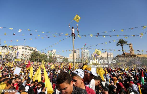 TOPSHOT Fatah supporters wave the party flag as they take part in a rally in Gaza City on November 11 2017 marking the death anniversary of late...