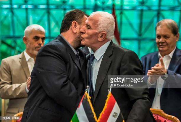 Fatah's Azzam alAhmad and Saleh alAruri of Hamas kiss after signing a reconciliation deal in Cairo on October 12 as the two rival Palestinian...
