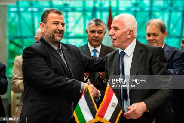 Fatah's Azzam alAhmad and Saleh alAruri of Hamas shake hands after signing a reconciliation deal in Cairo on October 12 as the two rival Palestinian...