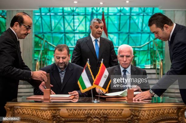 Fatah's Azzam alAhmad and Saleh alAruri of Hamas sign a reconciliation deal at the Egyptian intelligence services headquarters in Cairo on October 12...