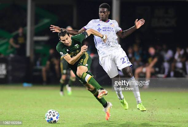 Fatai Alashe of FC Cincinnati fouls Diego Valeri of Portland Timbers during a round of sixteen match in the MLS Is Back Tournament at ESPN Wide World...