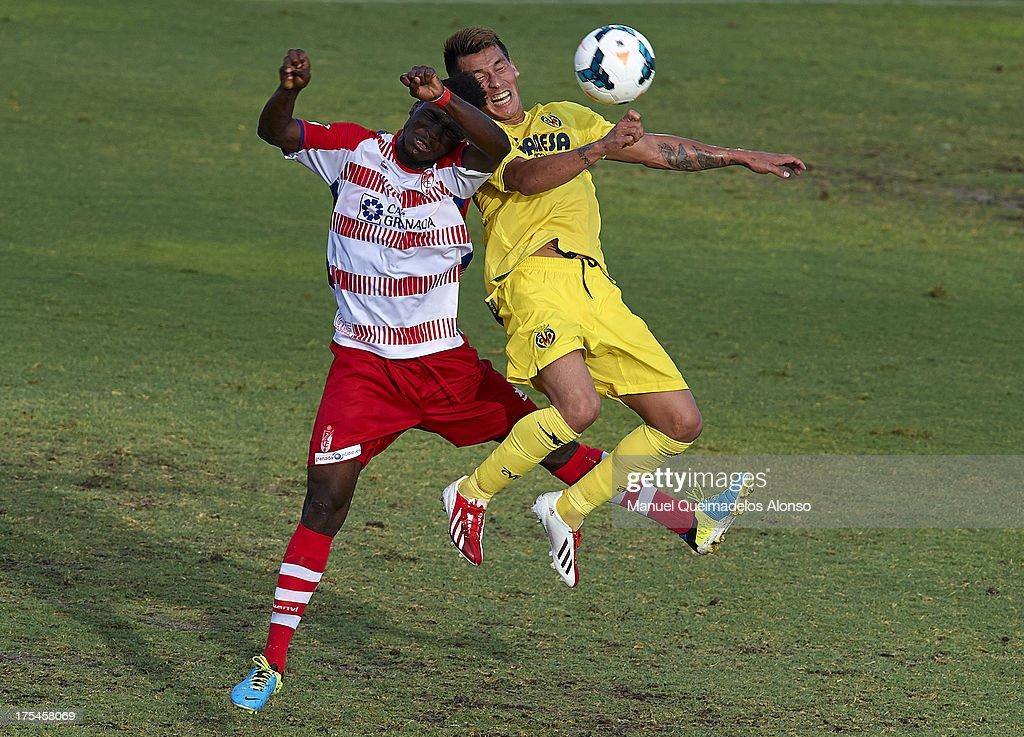 Fatau (L) of Granada competes for the ball with Hernan Perez of Villarreal during a friendly match between Villarreal CF and Granada FC at La Manga Club on August 03, 2013 in La Manga, Spain.