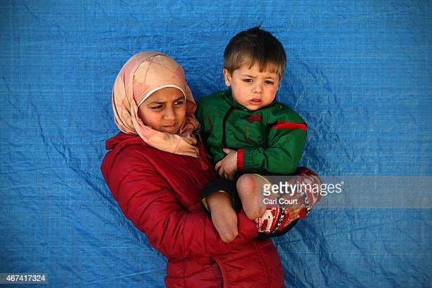 Fatemah Aldan holds her 2 year old brother Saif who lost both legs during a barrel bomb attack on their home town of Aleppo as they wait for...