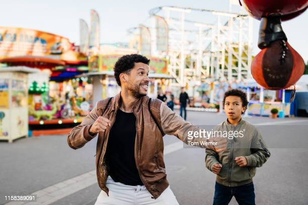 father about to hit punching bag at fun fair - gripping stock pictures, royalty-free photos & images