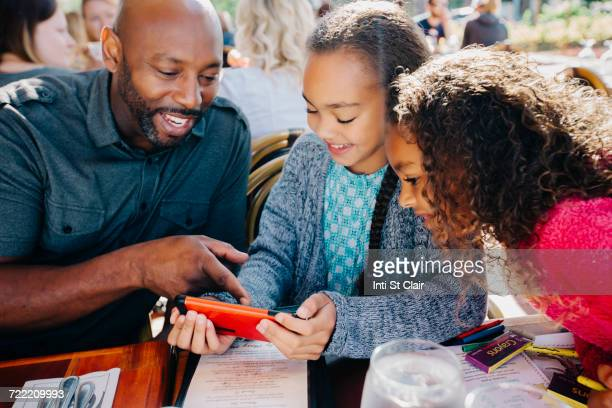 Father ad daughters texting on cell phone at restaurant