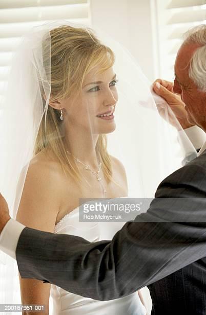 Father adjusting daughter's bridal veil, smiling