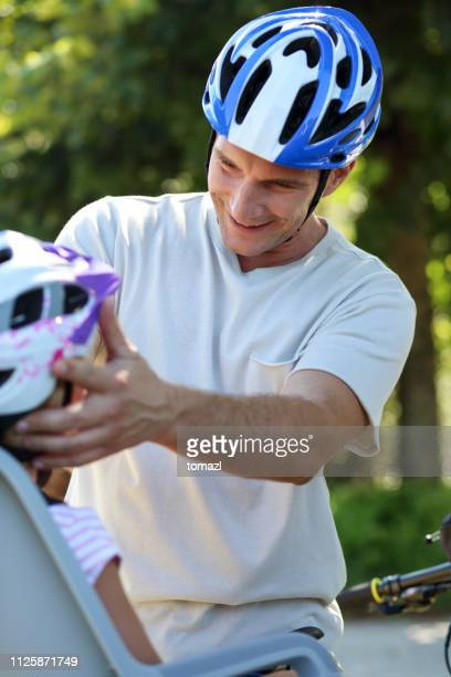father adjusting his son's cycling helmet - cycling helmet stock photos and pictures