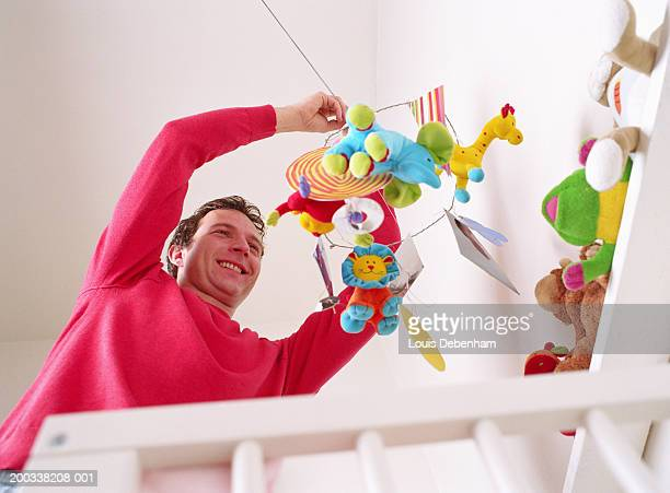 Father adjusting mobile over cot, smiling, low angle view