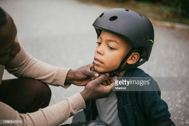 father adjusting son's helmet on footpath - protection stock pictures, royalty-free photos & images