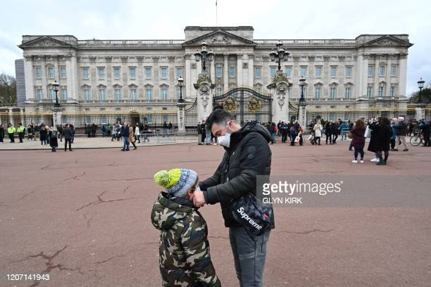 Father adjusts his son's mask between the Queen Victoria Memorial and Buckingham Palace in London on March 14, 2020. - British Prime Minister Boris...
