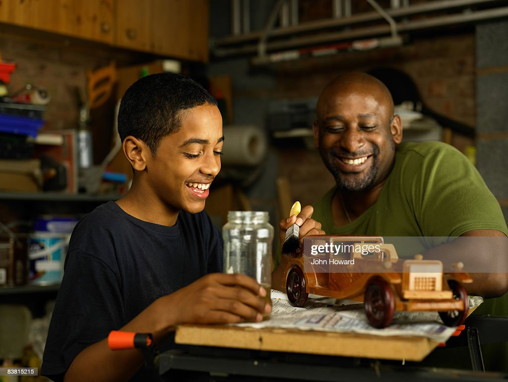 Father admiring Son's woodwork project : Stock Photo