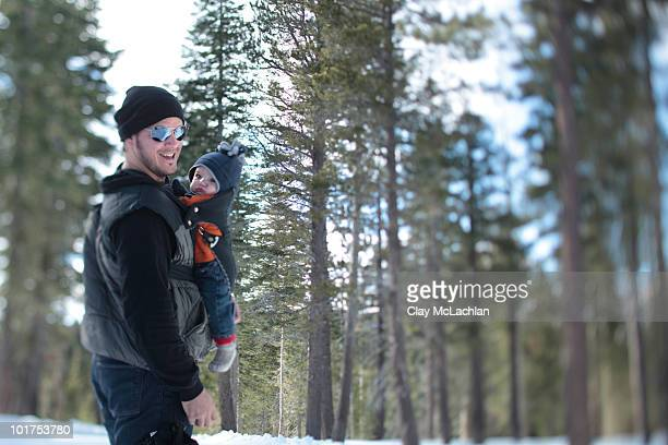 A father, age 35, walk with his son, age 4 months, in the snow covered wilderness of Lake Tahoe, Calfornia.