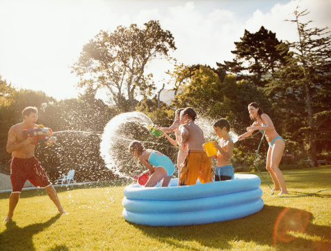 Father Aims a Water Gun at Children Throwing Water in a Paddling Pool - gettyimageskorea