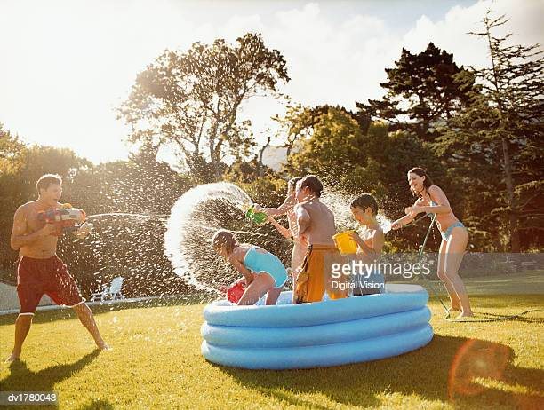 father aims a water gun at children throwing water in a paddling pool - spuiten activiteit stockfoto's en -beelden