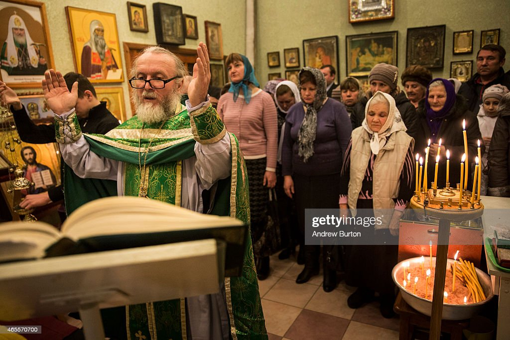 Father Alexandr Matveev leads his congregation in prayers in the office space of Saint Johan Krondshtadsky Church on March 8, 2015 in the Petrovskiy district of Donetsk, Ukraine. The main hall of the Russian Orthodox church was destroyed by shelling in the summer of 2014, forcing the congregation to meet in the office space of the church since then.