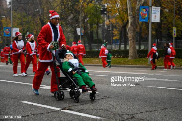Father an son dressed as Santa Claus running during the annual Santa Claus Christmas race.
