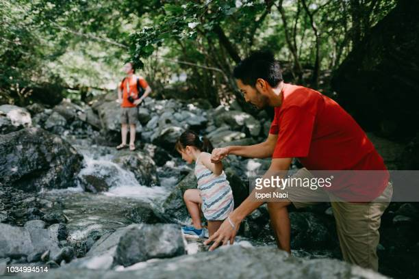 Father and 4 year old child hiking together in river