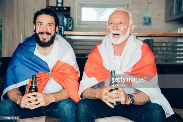 father and a son supporting different soccer teams watching game together - mens world championship stock photos and pictures