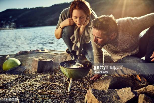 father and adult daughter at the riverside having a barbecue - simple living stock pictures, royalty-free photos & images